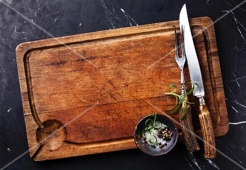 Cutting board, seasonings and rosemary with fork and knife carving set on dark marble background