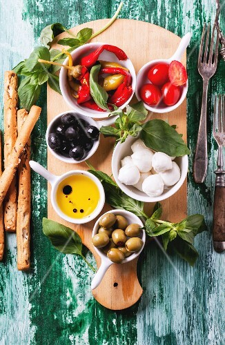 Mixed antipasti olives and mozzarella served on wooden cutting board over green wooden table