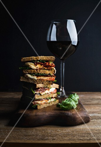 Panini with whole grain bread, mozzarella, cherry and dried tomatoes, basil served with glass of red wine