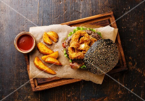 Black burger with sesame seed bun, meat, bacon, onion rings fries and potato wedges on dark wooden background