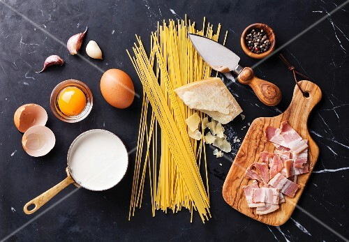 Ingredients for Pasta Carbonara on dark marble background