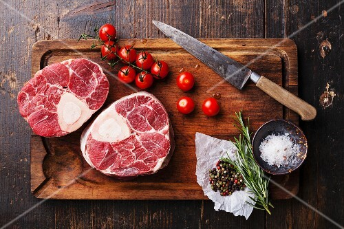 Raw fresh cross cut veal shank and seasonings for making Osso Buco on wooden cutting board