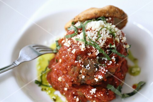 Large meatball with grated parmesan cheese and shredded basil