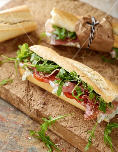Rustic baguette with serrano ham, salami, rocket and tomato