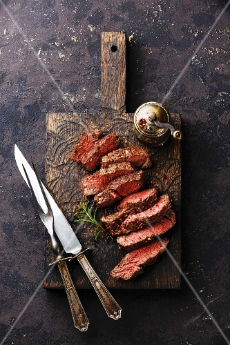 Sliced medium rare grilled Beef steak with knife and fork for meat on wooden cutting board background