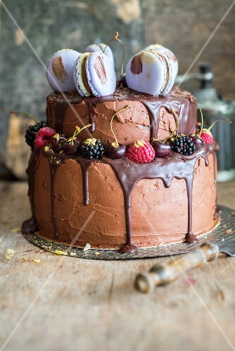 A chocolate cake decorated with macarons and berries