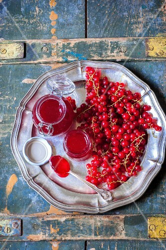 Redcurrant jam in glass jars on a metal plate