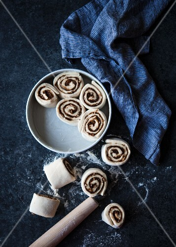 Unbaked cinnamon rolls in and next to a baking tin