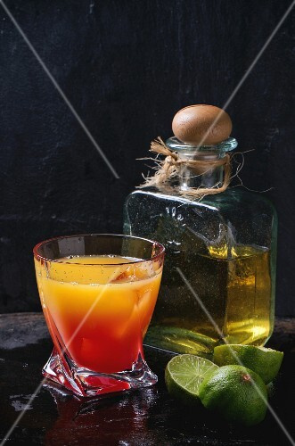 Glass of tequila sunrise cocktail, served with bottle of tequila anejo sliced limes over black background