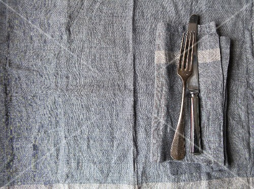 Grey linen place setting with matching grey linen napkin and vintage silver knife and fork