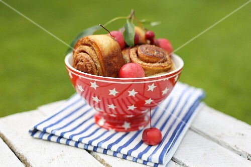 Cinnamons rolls in a red bowl and paradise apples