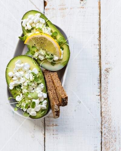 Healthy lunch: stuffed avocado with cottage cheese, rucola sprouts, rye bread and lemon