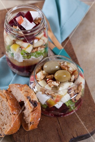 Beetroot with goat's cheese, apple, walnuts, olives and onions in a glass jar