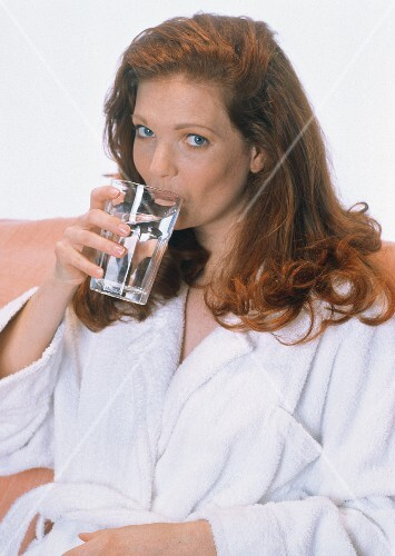Woman in Bathrobe Sipping Glass of Water