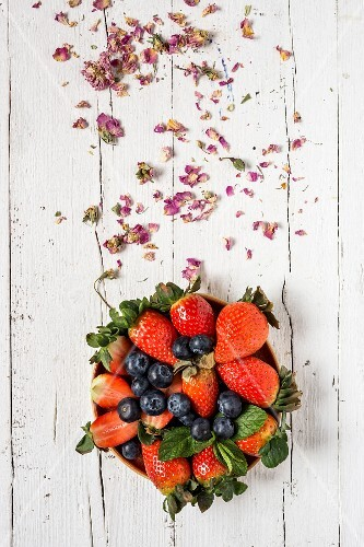 Mix of strawberries and blueberries on old wooden table