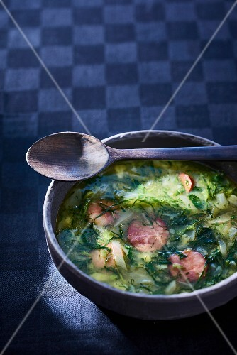 Herb soup with slices of sausage