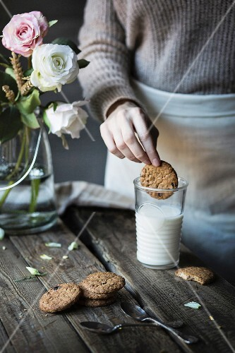 Woman dipping a biscuit in a glass of milk