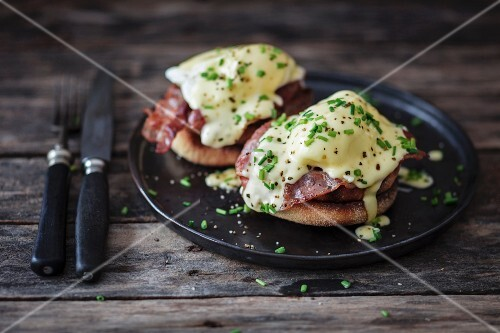 Eggs Benedict on a black plate