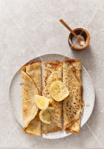 three rolled pancakes pn a off white texture plate with lemon wedges on a stone surface propped with wooden sugar bowl and spoon