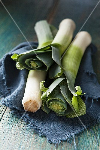 Three whole leeks on a blue cloth and green wooden surface
