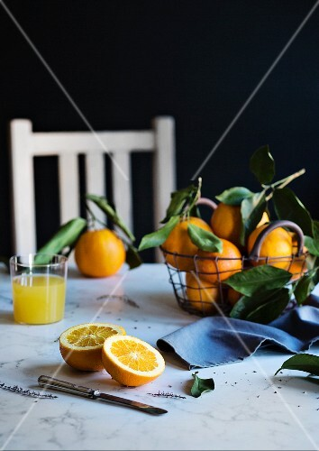 Orange juice and fresh oranges on the table