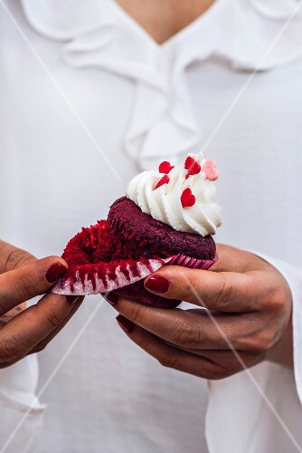 A woman with a white dress is holding a red velvet cupcake in her hand, removing the liner