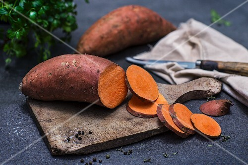 Sweet potato, sliced, on a chopping board