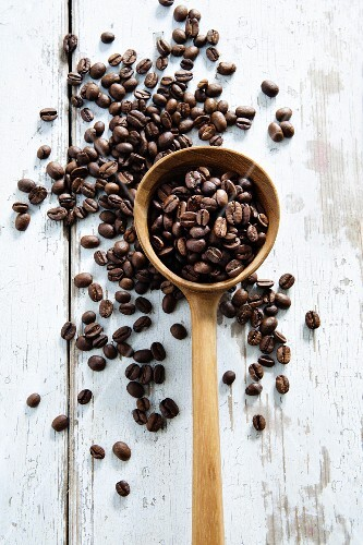 Coffee beans scattered on a table and in a wooden ladle