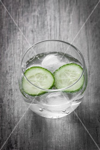 A glass of water with cucumber slices and ice cubes