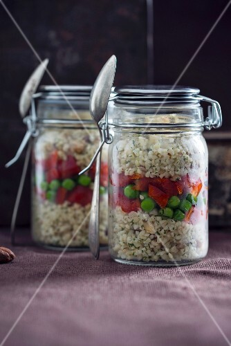 Bulgur wheat salad with hazelnuts, peppers and peas in glass jars