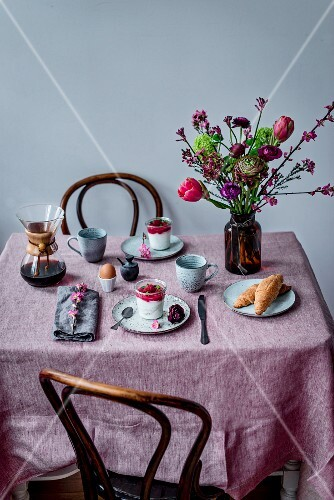 A breakfast table laid with coffee, coconut milk yoghurt, raspberries, an egg, spelt croissants and a flower bouquet