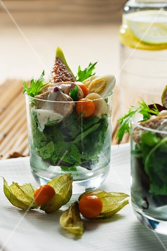 Rocket salad with chicken breast, figs, physalis and quail eggs in glasses