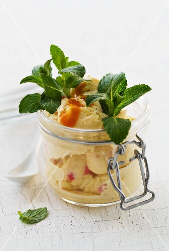 Vanilla and strawberry ice cream with fruit sauce and mint in a mason jar