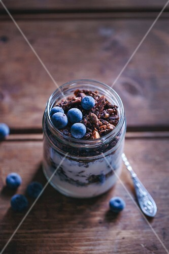 Chocolate granola and yogurt breakfast jar topped with blueberries