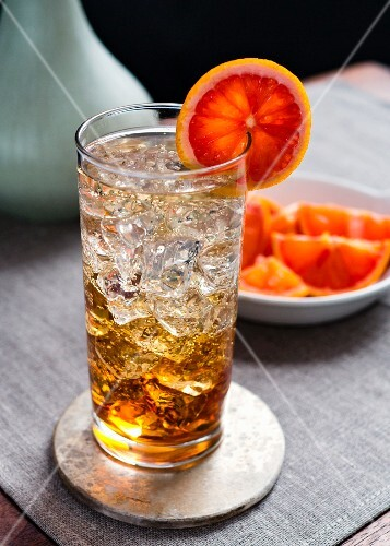 Spritzer in collins glass with ice and bloodorange garnish