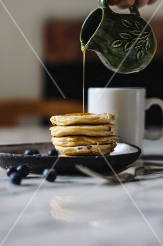 Syrup pouring from a jug onto a pile of pancakes