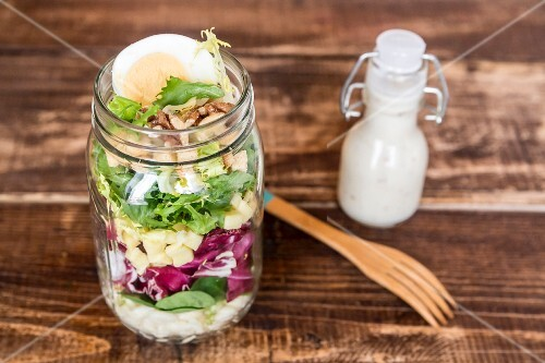 Orzo pasta with lambs lettuce, radicchio, endive, croutons, cheese, walnuts and eggs in a glass jar with dressing and a wooden fork