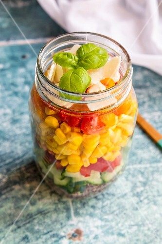 A colourful salad in a glass jar with red quinoa, cucumber, peppers, corn, tomatoes, pecorino and basil
