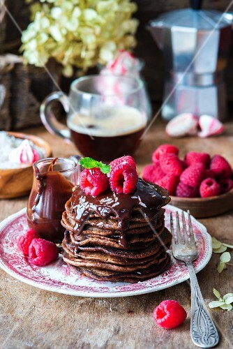 A stack of pancakes with chocolate sauce and raspberries