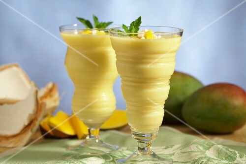 Two glasses of mango smoothie with coconut