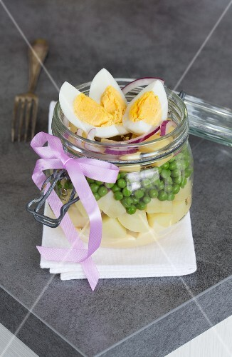 A vegetable salad with potatoes, peas, cheese, onions, mayonnaise and egg in a glass jar
