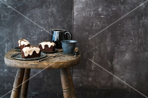 Glazed espresso friands on a rustic wooden stool against a dark background