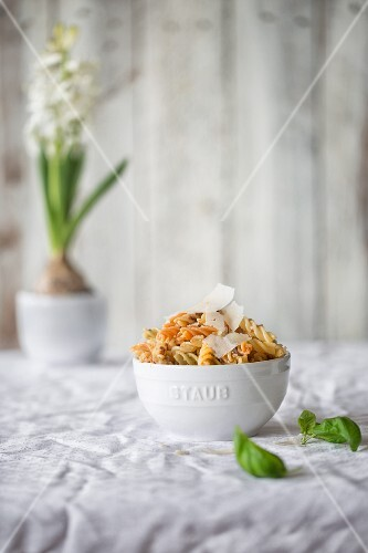 Colourful fusilli with pesto and parmesan in a white bowl on a table