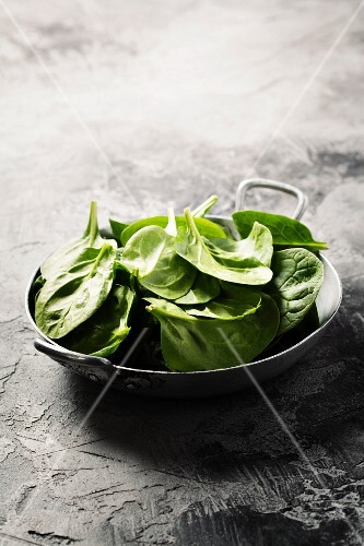 Fresh green spinach on rustic background