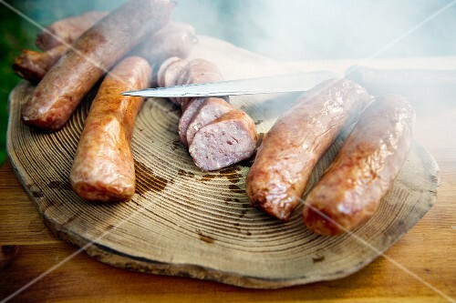Smoked sausages with a knife on a wooden slab