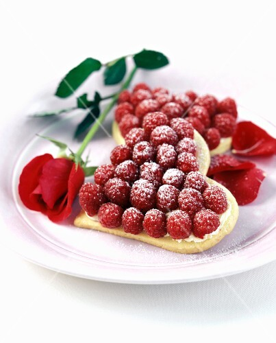 Shortbread hearts with raspberries on plate; rose