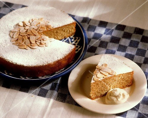 Almond cake & a piece of almond cake with cream on plate
