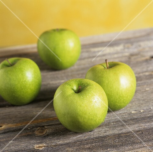 Four Granny Smith apples on wooden background