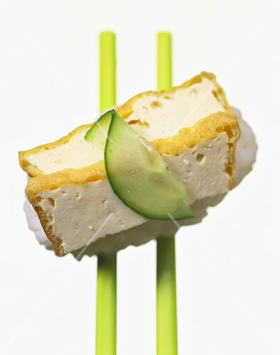 Nigiri-sushi with baked tofu strips and slice of cucumber