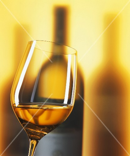 A glass of white wine with wine bottles in background
